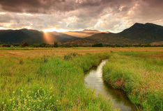 Colorful sunset sunbeams above a stream in Heber Valley. Sunset rays above a stream in rural Utah, USA Royalty Free Stock Photography