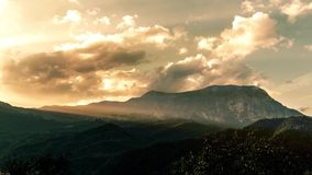 Colorful sunset timelapse over mountain landscape. Moving clouds with dramatic light stock footage