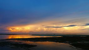 Colorful sunset. A very calm, colorful sunset video from Siquijor Island shores. Reflection of the sky can be seen on the puddles between the seaweed covered stock video footage