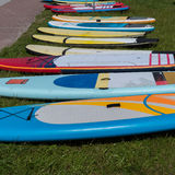 Colorful surf boards lying in the grass waiting to be used Stock Photography