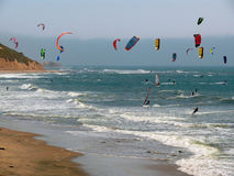 Colorful surf kites. A lot of colorful kites and windsurfers in a windy area on the Pacific Coast California near Santa Cruz. Mountains on the left side and the Stock Photos