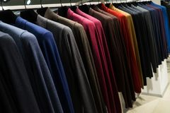 Colorful sweaters hanging in clothing retail store. Stock Photo