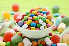 Sweet candies in bowl. Colorful sweet candies in bowl on green background royalty free stock photo