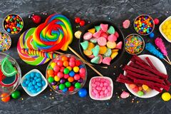 Colorful sweet candy buffet table scene, above view over dark stone