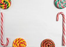 Colorful sweet candys on blank notepad. striped Candy Canes and spiral lollipops on paper exercise book in a cell, mockup.  royalty free stock photography