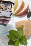Colorful sweet creamy cake on the plate decorated with mint and Stock Images