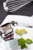 Colorful sweet creamy cake on the plate decorated with mint and Stock Photo