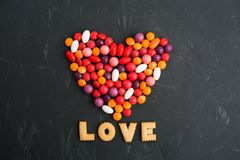 Colorful sweet heart of many candies with LOVE. Over grey background with copy space; flat lay Royalty Free Stock Photo