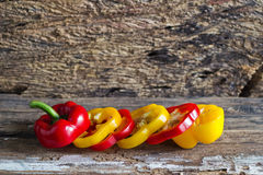 Colorful sweet pepper slices decoration on wooden background Royalty Free Stock Images