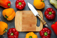 Colorful sweet pepper on table with empty cutting board and knif Stock Photo