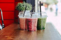 Colorful Sweet smoothie in plastic cups on wooden table royalty free stock images