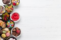 Colorful sweets. Lollipops, macaroons, marshmallow, marmalade and candies. Top view with space for your greetings stock photography