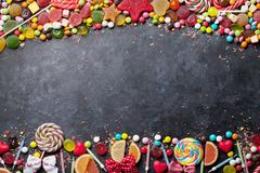 Colorful sweets. Lollipops, macaroons, marshmallow, marmalade and candies. Top view with space for your greetings stock images