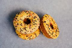 Sweets food - three yellow donuts on gray background stock photo
