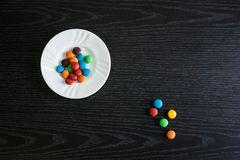 Colorful and sweets objects on the table. Some colorful and tasty candies over a dark wooden table royalty free stock photography