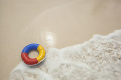 Colorful swim ring. Travel or safety background with a colorful swim ring floating to the beach Stock Photos