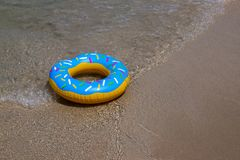 Colurful inflatable donut on the seashore. with soft wave of blue ocean in outdoor sun lighting on sandy beach. Background of travel in summer season royalty free stock photography