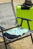Colorful swimsuits on folding chair and suitcase Stock Images