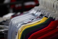 Colorful t-shirts on hang for sale in shop. Multicolored summer polo on hanger.