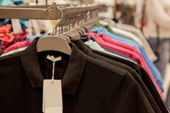 Colorful t-shirts on hangers. Men`s stylish clothes. Showcase, sale, shopping. Fashion and trade concept