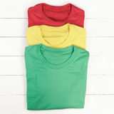 Colorful t-shirts. Red, green and yellow folded t-shirts on white wooden background Royalty Free Stock Photo