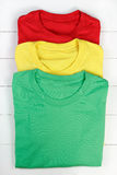 Colorful t-shirts. Red, green and yellow folded t-shirts on white wooden background Stock Photography