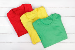 Colorful t-shirts. Red, green and yellow folded t-shirts on white wooden background Royalty Free Stock Photos