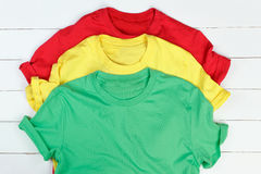 Colorful t-shirts. Red, green and yellow t-shirts on white wooden background Stock Photo