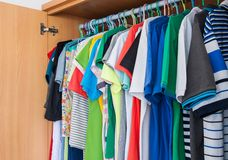 Colorful t-shirts in wardrobe. Stock Photo