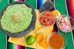 Colorful Table Setting for Mexican Appetizers. Fresh guacamole with avocado seed in traditional Mexican molcajete mortar and pestle and variety of salsas, chips Stock Photo