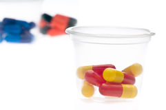 Colorful tablets, capsules in a cup Royalty Free Stock Photos