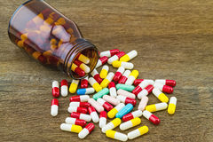 Colorful tablets medicine in black bottle on wooden background Stock Photo