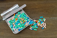 Colorful tablets medicine in the drug counting tray on wooden ba Stock Photo