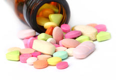 Colorful tablets spilled out bottles Royalty Free Stock Images