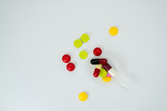 Colorful tablets in teaspoon and many pills spread. On a white background Royalty Free Stock Image