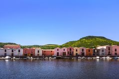 Colorful tannery houses on a canal with boats and green mountain range in the background, Bosa, Sardinia, Italy stock photography