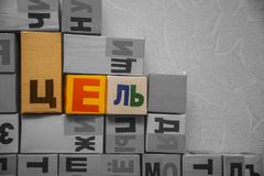 Colorful target word in Russian language. Among grey cubes with letters Stock Photography