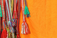 Colorful tassels of a hippie belts on orange background. Stock Photos