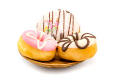 Colorful tasty doughnuts in wooden plate Royalty Free Stock Photos