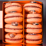 Colorful and tasty Macaroons in paper box with wedding rings Stock Image