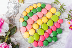 Colorful tasty macaroons on wooden table with flowers, a french sweet delicacy, macaroon texture. Top view Royalty Free Stock Photography