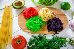 Colorful tasty pasta on board and raw vegetables on rustic table. Flat lay. Top view Stock Photo