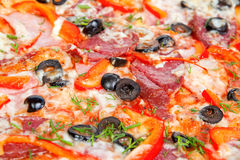 Colorful tasty pizza. With olives, pepperoni, ham and pepper, close-up shot Royalty Free Stock Image