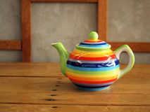 Colorful teapot on wood planks Royalty Free Stock Photo