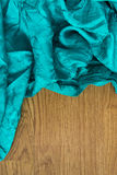 Colorful textile close up in bright green-blue on wood Stock Image