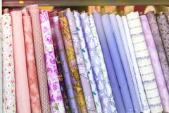 Different colored pills of cloth fabrics textile neatly folded for display royalty free stock photos