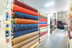Colorful textile fabric material rolls in warehouse Stock Photos