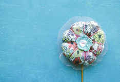 Colorful textile flower on stick. Handmade toy isolated on turquoise background Stock Photo