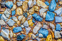 Colorful texture of wet stones. And sand. Blue, brown and gray cobbles and orange sand. Natural rock formation pattern, background or wallpaper Stock Images