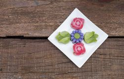 Colorful Thai layer cake design in different flower shape on white plate. Over old wooden table background Stock Photography